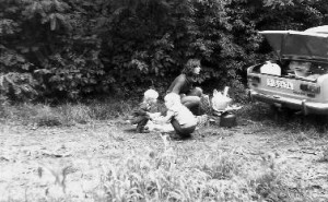 Peter's wife and children preparing a picnic meal while hiding behind the family car